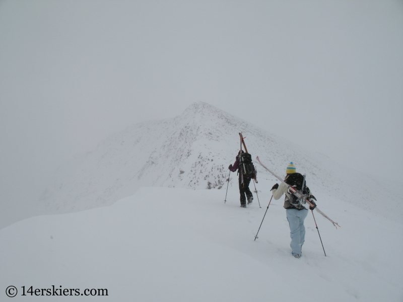 Climbing Culebra Peak to do backcountry skiing.