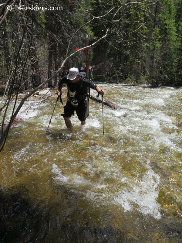 Mark Cavaliero crossing a stream on the way to backcountry ski on Mount Elbert northwest gullies.