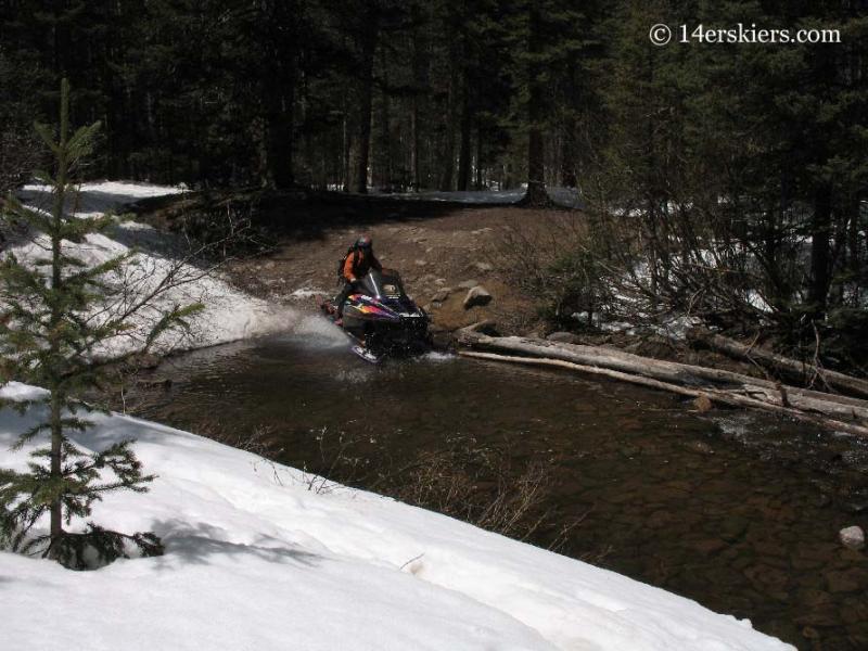 Frank Konsella snowmobiling across a stream.