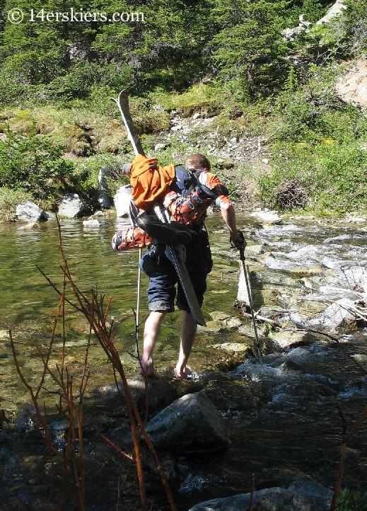 Frank Konsella crossing creek to ski Huron Peak