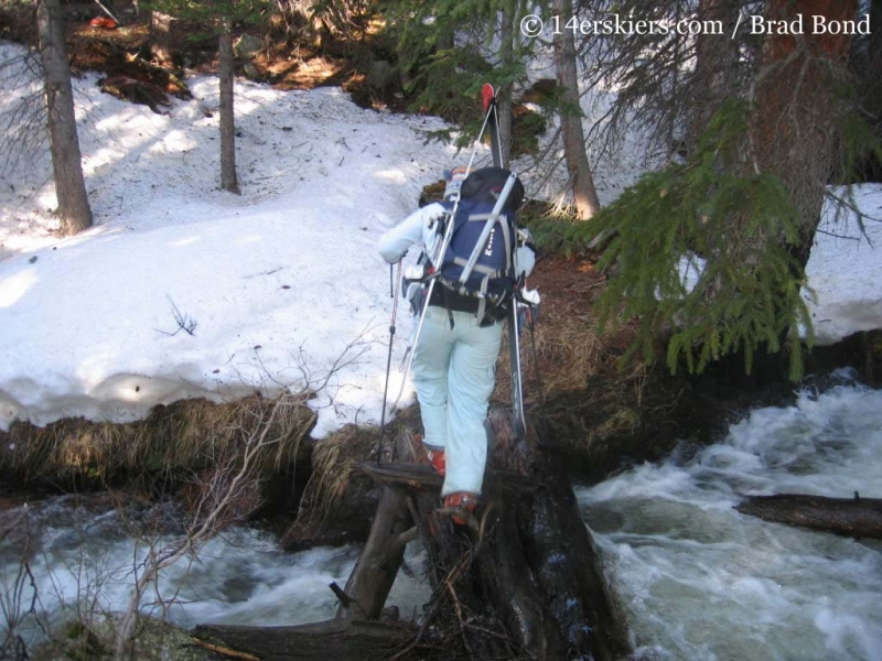 Brittany Walker Konsella crossing a bridge to go backcountry skiing on Tabeguache.