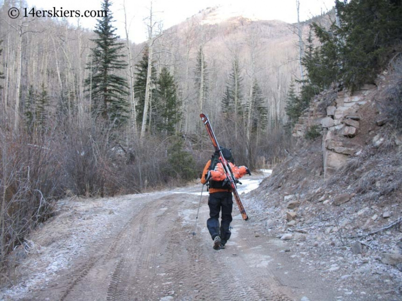 Frank Konsella hiking Nellie Creek Road to ski Uncompahgre